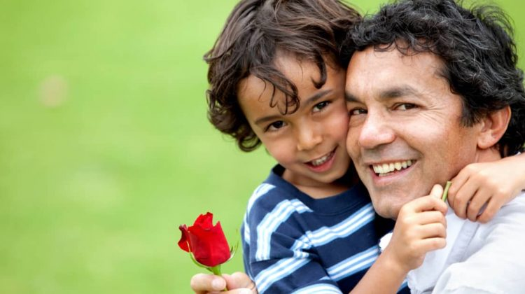 father cuddling his son while holding a red rose