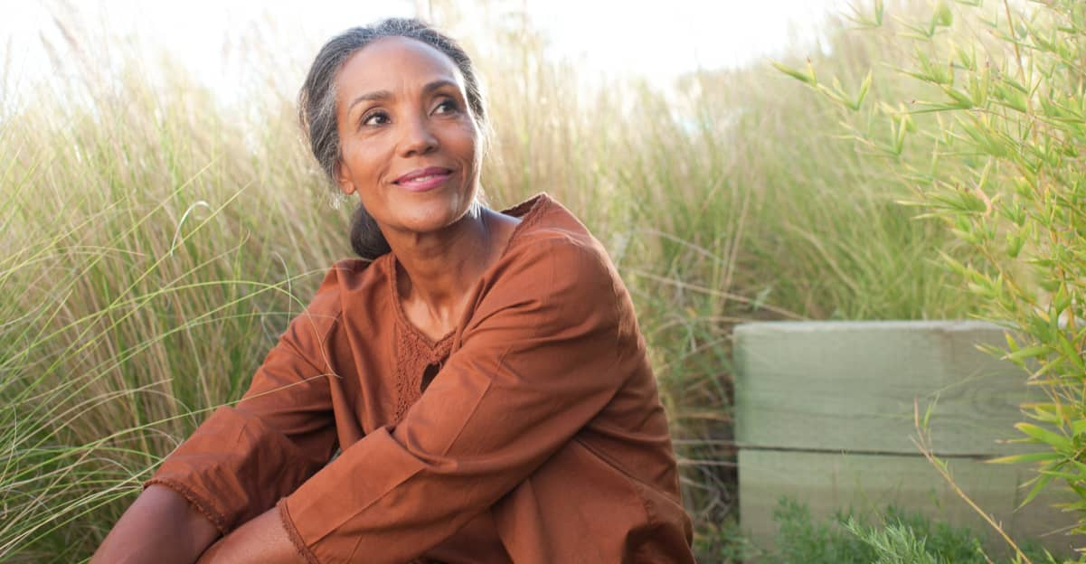 mature woman sitting on a bench, looking content