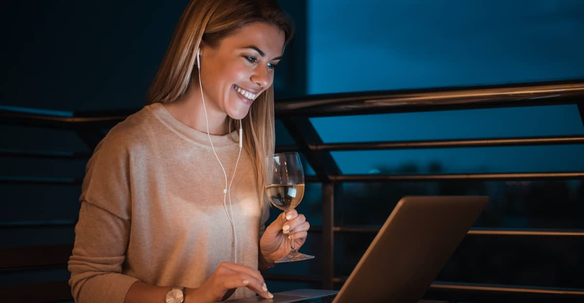 young woman at her laptop, on a video call, while drinking a glass of wine