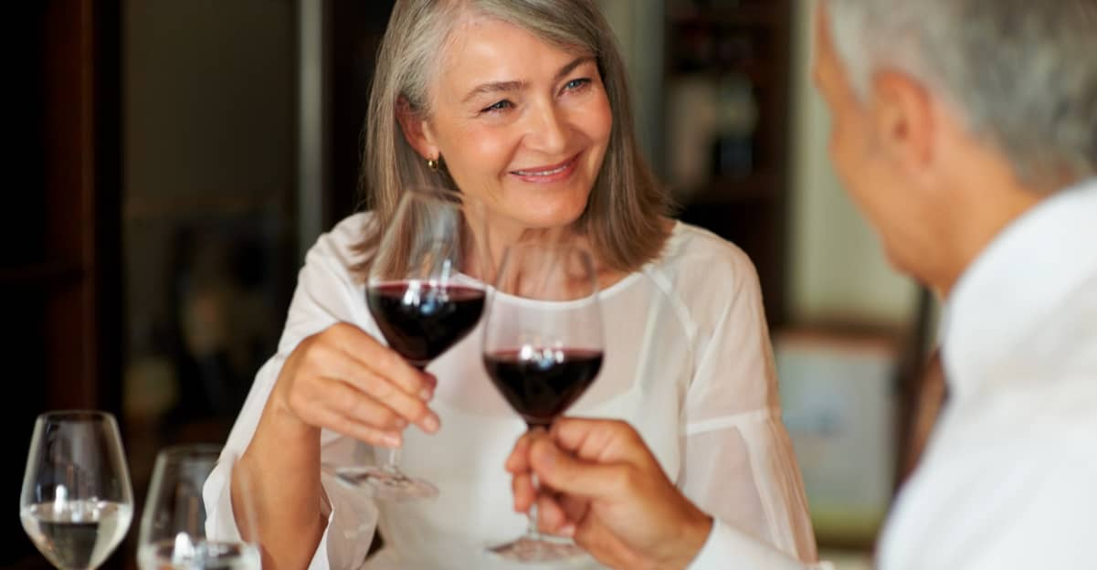 mature man and woman sharing a glass of red wine