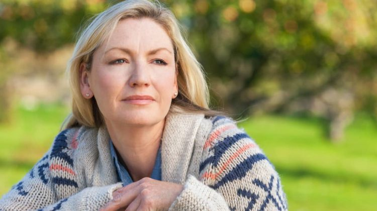 mature woman in her garden, looking thoughtful