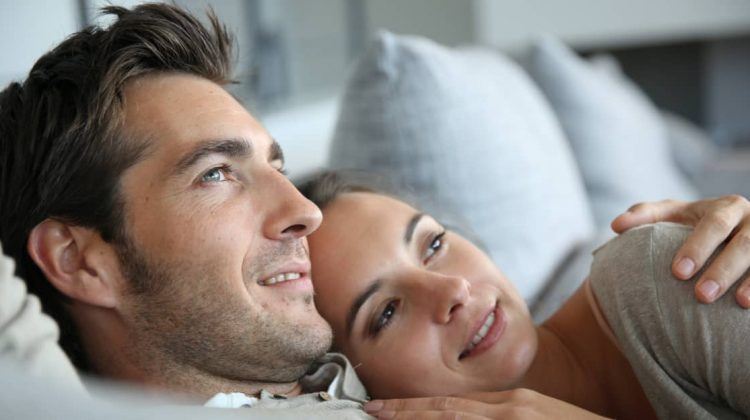 man and woman snuggling on a sofa